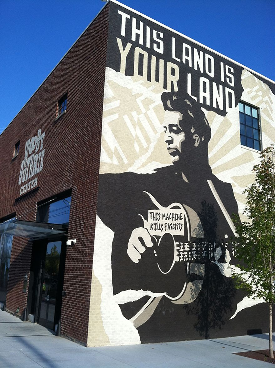 #10. OKLAHOMA $1.986/GALLON - This Sept. 26, 2014 photo shows the Woody Guthrie Center in Tulsa, Oklahoma's Brady Arts District. Guthrie was an Oklahoma native and the center honors his life and legacy. You'll have to pay to visit the museum but the evocative mural outside lends a distinctive feel to the neighborhood. The Brady Arts District has a trendy, hipster vibe and is dotted with art and music venues, along with cafes and bars. (AP Photo/Beth J. Harpaz)