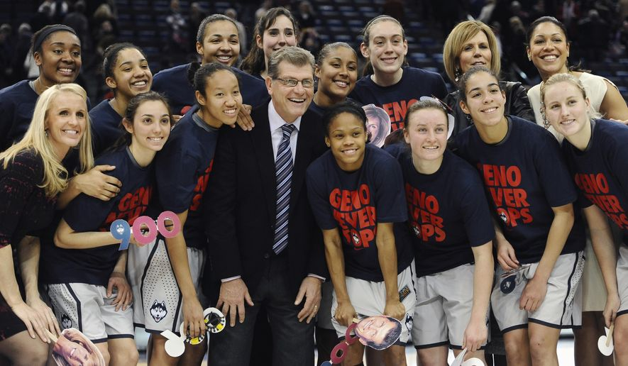 Connecticut coach Geno Auriemma, center, poses for a photograph with his team after his 900th career win, in an NCAA college basketball game against Cincinnati, Tuesday, Feb. 3, 2015, in Hartford, Conn. UConn won 96-36. (AP Photo/Jessica Hill)