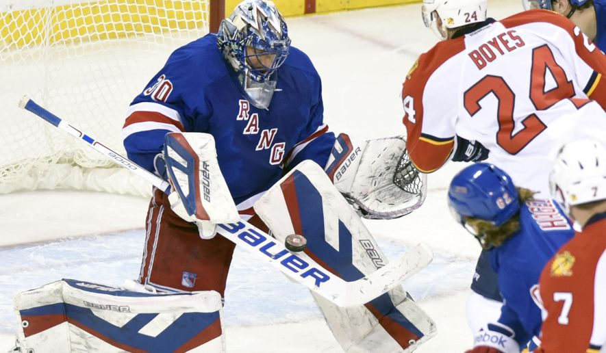 New York Rangers goaltender Henrik Lundqvist, left, deflects the puck as Florida Panthers' Brad Boyes (24) skates in during the third period of an NHL hockey game Monday, Feb. 2, 2015, at Madison Square Garden in New York. The Rangers won 6-3. (AP Photo/Bill Kostroun)