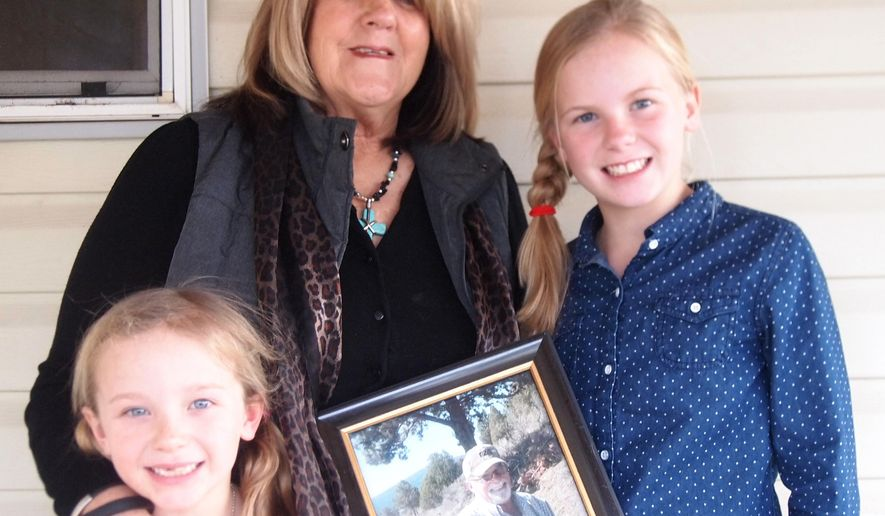 Kaye Cory, center, holds a picture of her husband Lyle with two of her grandchildren. Lyle, a Vietnam War veteran, died last November and Cory believes more could have been done to treat his heart condition and ensure his survival. (AP Photo/Klamath Falls Herald and News, Tristan Hiegler)