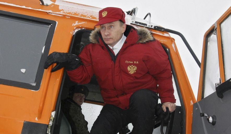 Then Russian Prime Minister Vladimir Putin jumps off a cross-country vehicle as he arrives to a research institute at the Franz Josef Land archipelago in the Arctic Ocean, April 29, 2010. (Associated Press) ** FILE **