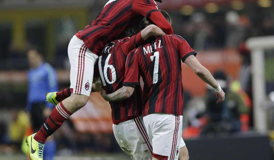 AC Milan's Jeremy Menez, right, celebrates with his teammates Salvatore Bocchetti, left, and Andrea Poli after scoring during a Serie A soccer match between AC Milan and Parma, at the San Siro stadium in Milan, Italy, Sunday, Feb.1, 2015. (AP Photo/Luca Bruno)