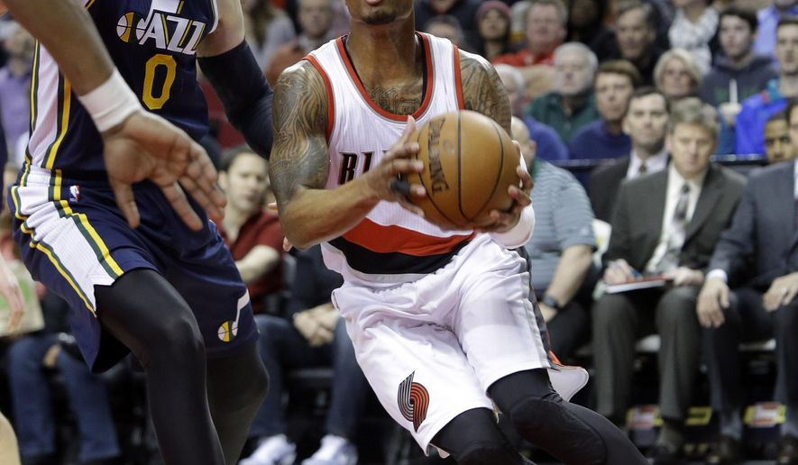 Portland Trail Blazers guard Damian Lillard, right, drives to the basket past Utah Jazz center Enes Kanter, from Turkey, during the first half of an NBA basketball game in Portland, Ore., Tuesday, Feb. 3, 2015. (AP Photo/Don Ryan)