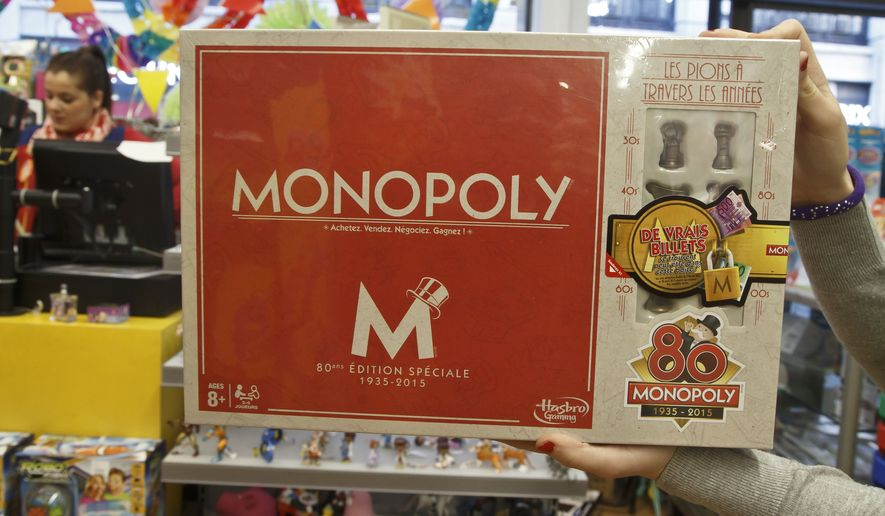 A saleswoman displays the new Monopoly board game version at a toy store near the Champs Elysees avenue in Paris, Wednesday, Feb. 4, 2015. The French version of Monopoly is celebrating its 80th year by slipping cash into 80 boxes of the game. One box will have the full complement in real money  20,580 euros ($23,600) as well as the Monopoly money needed to actually play the game, one of the most popular in France. 79 other boxes will have smaller amounts according to Hasbro. (AP Photo/Michel Euler)