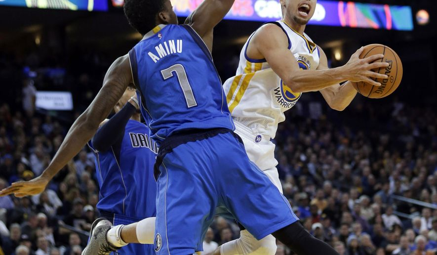 Golden State Warriors' Stephen Curry, right, looks for a shot as Dallas Mavericks' Al-Farouq Aminu (7) and another player defend during the second half of an NBA basketball game Wednesday, Feb. 4, 2015, in Oakland, Calif. Golden State won 128-114. (AP Photo/Marcio Jose Sanchez)