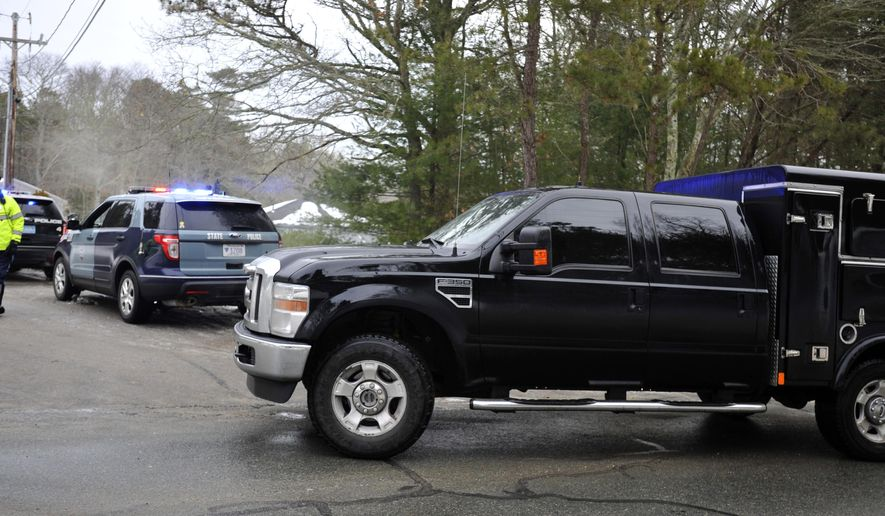 A bomb squad vehicle arrives at a Cape Cod condo community where one woman was shot to death and two other people, including a police officer, were wounded early Thursday, Feb. 5, 2015, in Bourne, Mass. Police said the bomb squad responded to examine items suspected of being hoax devices found there, allegedly placed by the shooting suspect who was taken into custody. (AP Photo/Cape Cod Times, Steve Heaslip)  MANDATORY CREDIT; MAGS OUT; NO SALES; TV OUT