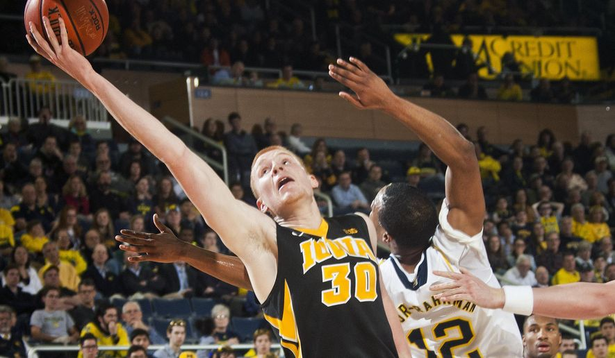 Iowa forward Aaron White (30) attempts to hook in a layup, defended by Michigan guard Muhammad-Ali Abdur-Rahkman (12), in the first half of an NCAA college basketball game at Crisler Center in Ann Arbor, Mich., Thursday, Feb. 5, 2015. (AP Photo/Tony Ding)