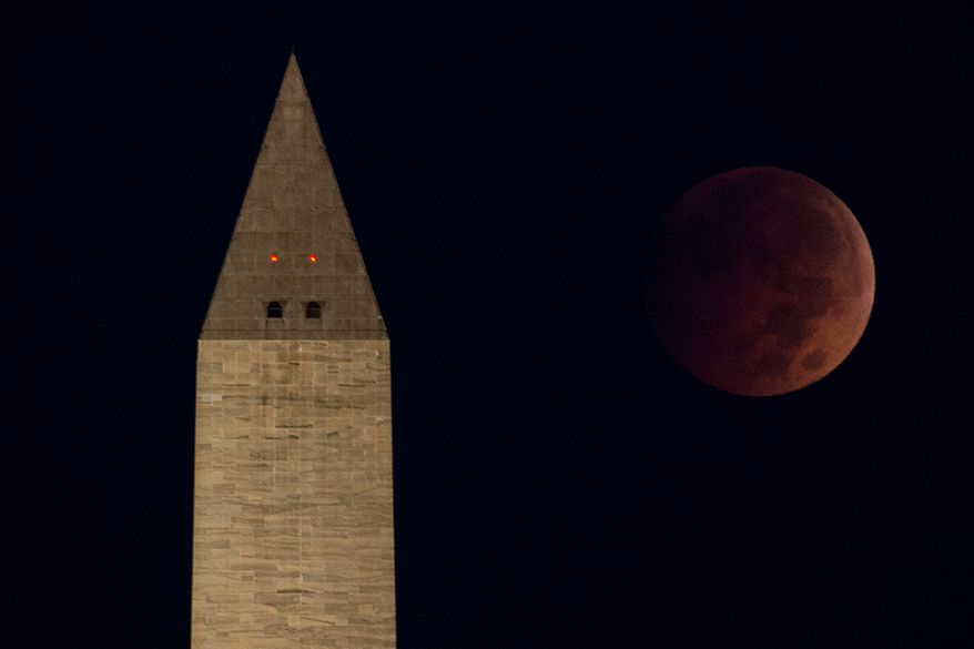 """12. WASHINGTON, D.C. -A """"blood moon"""" or lunar eclipse can be seen above the Washington Monument just before dawn on the National Mall, Washington, D.C., Wednesday, October 8, 2014. The lunar eclipse is the second and last of 2014. (Andrew Harnik/The Washington Times)"""