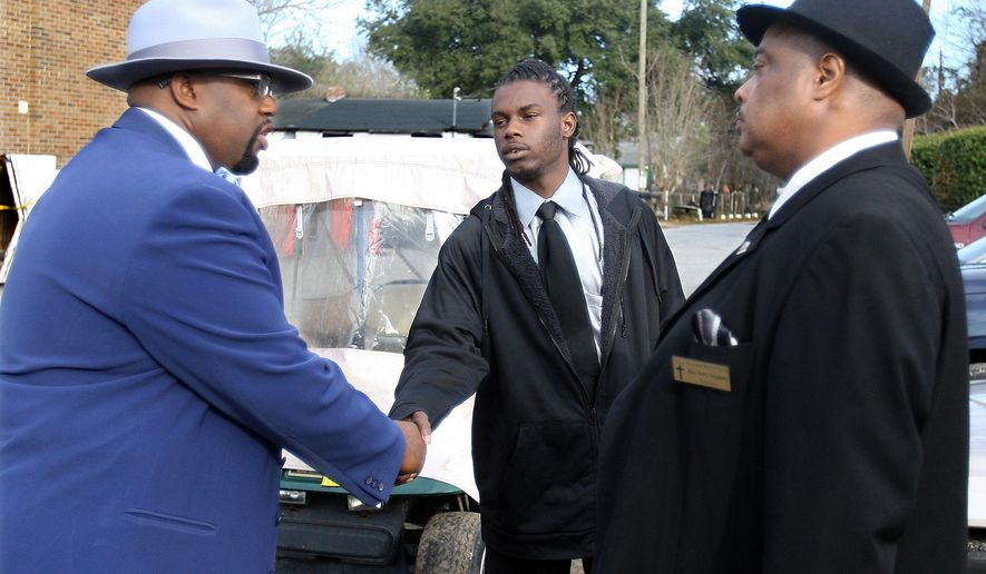 Desmond Casey, center,) is greeted by minister Sidney Melvin, left, and Terry Gradney on Jan. 25, 2015 at Charity Missionary Baptist Church, in North Charleston, S.C.  Casey survived being stabbed seven times in the face, six times in the back and four times in the arm after breaking up a fight between a man and a woman, and has a new outlook in life.  (AP Photo/The Post and Courier, Leroy Burnell)