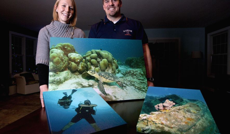 ADVANCE FOR USE SUNDAY, FEB. 8 AND THEREAFTER - In this Jan. 7, 2015 photo, Rebecca and Kyle Cline, of Maroa, Ill., stand next to a few photos from their diving trips while they were living in Piracicaba, Brazil. The couple works for Caterpillar as engineers and were living and working from Brazil for the last three years. (AP Photo/Herald & Review, Danny Damiani)