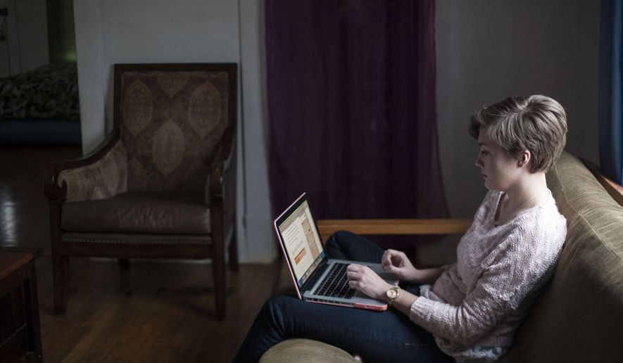 ADVANCED FOR RELEASE MONDAY, FEBRUARY 9, 2015 Kelly Rothe, 21, an Eastern Michigan University student who had a double mastectomy last May, writes a paper on her laptop for school on Friday, Dec. 5, 2014, in Ann Arbor, Mich. (AP Photo/The Ann Arbor News, Katie McLean)