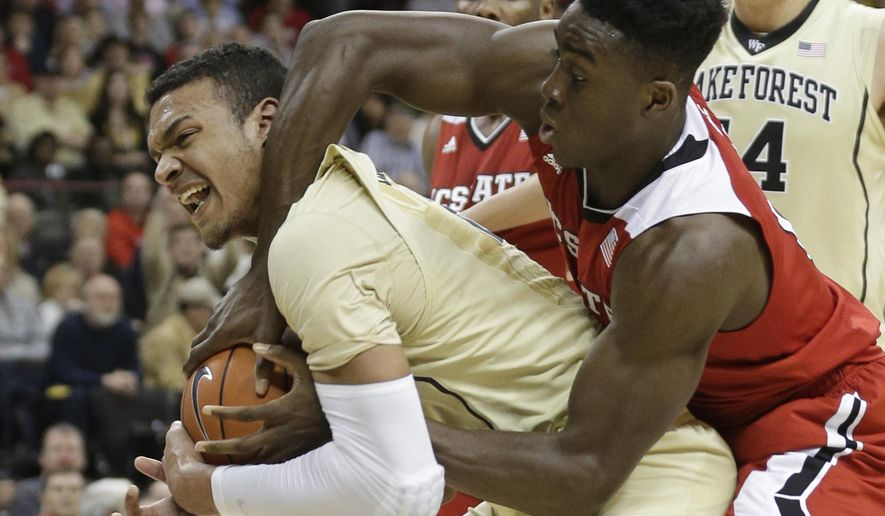 North Carolina State's Abdul-Malik Abu, right, fouls Wake Forest's Devin Thomas, left, during the second half of an NCAA college basketball game in Winston-Salem, N.C., Tuesday, Feb. 3, 2015. Wake Forest won 88-84. (AP Photo/Chuck Burton)