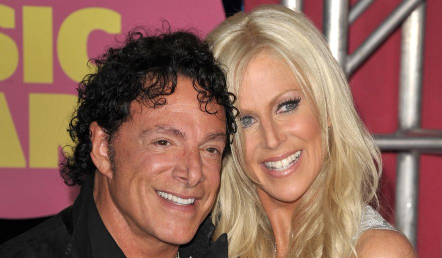 Neal Schon, left, and Michaele Salahi arrive at the CMT Music Awards in Nashville, Tenn., in this June 6, 2012, file photo. Schon, the lead guitarist and founder of the iconic San Francisco rock band Journey, sued the city Friday, Feb. 6, 2015, over a $240,000 fee to use a city landmark for his lavish wedding to former reality television star Salahi. (Photo by John Shearer/Invision/AP File)
