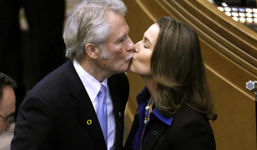 FILE - In this Jan. 12, 2015 file photo, Oregon Gov. John Kitzhaber kisses fiancee, Cylvia Hayes, after he is sworn in for an unprecedented fourth term as Governor in Salem, Ore.  Big political scandals are rare in Oregon, but there's a huge one swirling around Kitzhaber and Hayes as she faces allegations that she used her access to the governor's office to secure contracts for her consulting business and that she hasn't  reported all of her income to tax authorities.  (AP Photo/Don Ryan)