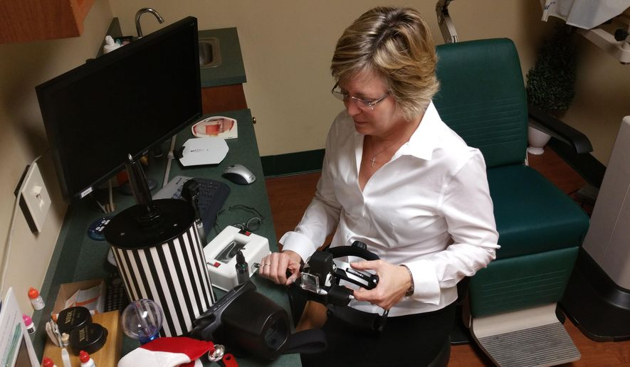 ADVANCE FOR USE SUNDAY, FEB. 8 - In this photo taken Jan. 19, 2015, optometrist Cathy Doty, of New Bern Family Eye Care, shows off an array of equipment used to conduct eye exams on children and special needs patients in New Bern, N.C. After more than 20 years of serving patients of all ages, Doty decided to dedicate the rest of her career to an underserved population, pediatrics and those with special needs. (AP Photo/The Sun Journal, Crystal Garrett)