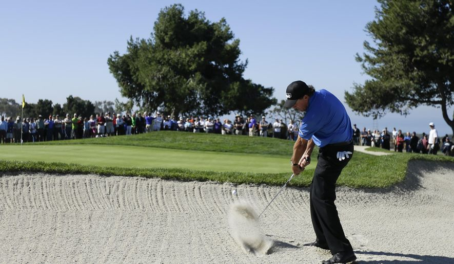 Phil Mickelson hits out of a bunker on the 14th hole of the North Course at Torrey Pines during the second round of the Farmers Insurance Open golf tournament Friday, Feb. 6, 2015, in San Diego. (AP Photo/Gregory Bull)