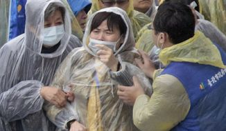 Relatives from mainland China react as they watch divers recover bodies at the site of a commercial plane crash in Taipei, Taiwan, Friday, Feb. 6, 2015. TransAsia Airways Flight 235 clipped a bridge shortly after takeoff and crashed into a river in the island's capital of Taipei on Wednesday morning. (AP Photo/Wally Santana)