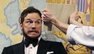 Actor Chris Pratt gets ready to break a board with his head during a roast at Harvard University, in Cambridge, Mass., Friday, Feb. 6, 2015. (Associated Press) ** FILE **
