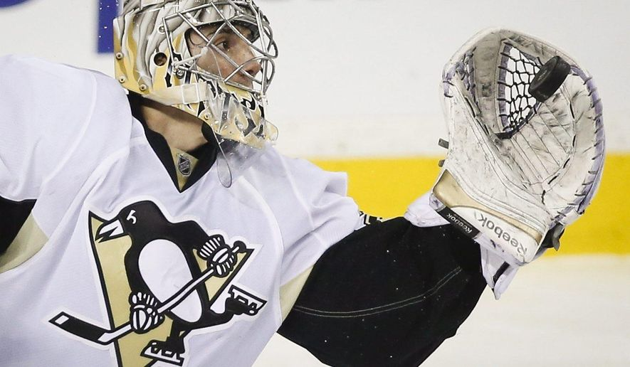 Pittsburgh Penguins goalie Marc-Andre Fleury grabs the puck during the second period on an NHL hockey game, Friday, Feb. 6, 2015 in Calgary, Alberta. (AP Photo/Canadian Press, Jeff McIntosh)