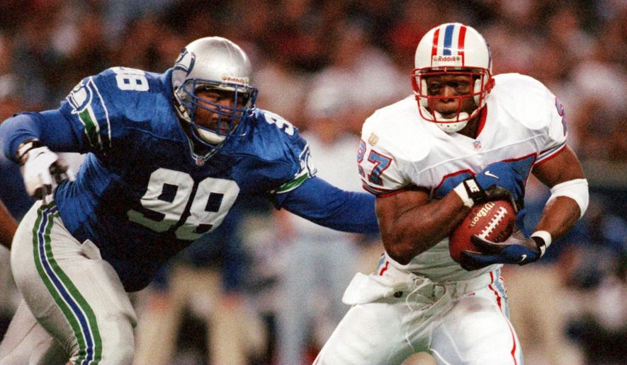 In this Nov. 3, 1996 file photo, former Seattle Seahawks defensive tackle Sam Adams, left, pursues Houston Oilers running back Eddie George during an NFL football game in Seattle. The state of Washington has filed criminal charges, Friday, Feb. 6, 2015 against Adams, saying he failed to pay taxes and stole wages from workers at fitness clubs he ran in Seattle and Tacoma, Wash. (AP Photo/The Seattle Times, Rod Mar, File)  SEATTLE OUT; USA TODAY OUT; MAGS OUT; TELEVISION OUT; NO SALES; MANDATORY CREDIT TO BOTH THE SEATTLE TIMES AND THE PHOTOGRAPHER