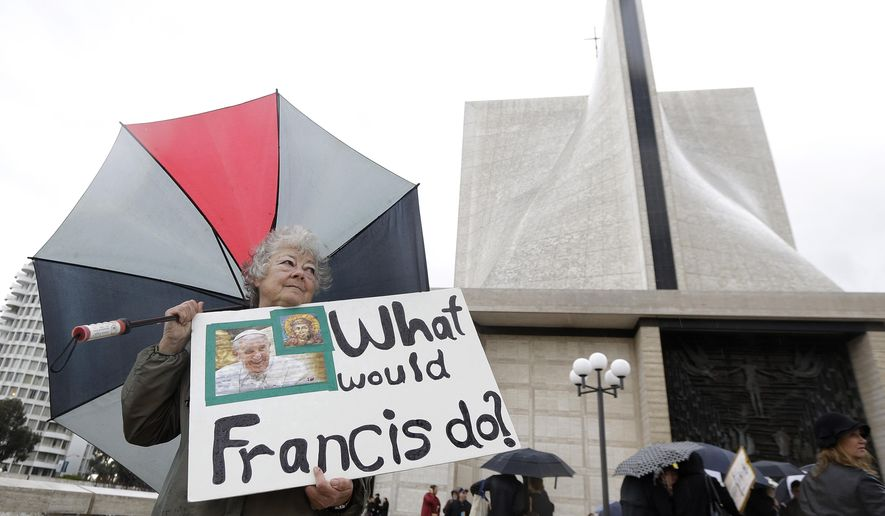 Marti Kashuba holds up a sign outside of St. Mary's Cathedral in San Francisco, Friday, Feb. 6, 2015. The Roman Catholic archbishop of San Francisco is getting pushback from some parents, students and teachers at parochial schools after unveiling faculty handbook language calling on teachers to lead their public and professional lives consistently with church teachings on homosexuality, same-sex marriage, abortion, birth control and other behaviors he describes as evil. (Associated Press) **FILE**