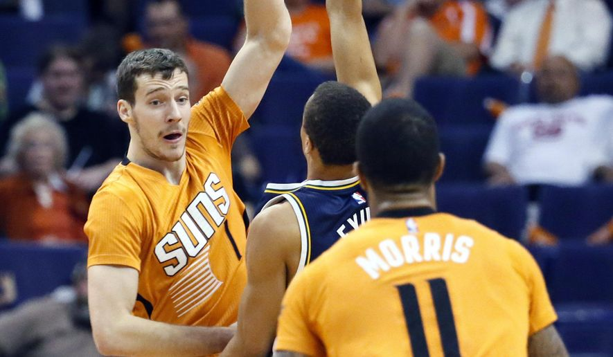 Phoenix Suns guard Goran Dragic (1), of Slovenia, passes to Markieff Morris (11) as Utah Jazz guard Dante Exum, of Australia, defends during the first half of an NBA basketball game, Friday, Feb. 6, 2015, in Phoenix. (AP Photo/Matt York)