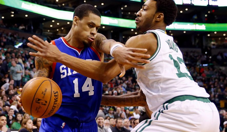Philadelphia 76ers guard K.J. McDaniels (14) tries to fight his way past Boston Celtics' James Young during the second quarter of an NBA basketball game in Boston on Friday, Feb. 6, 2015. (AP Photo/Winslow Townson)