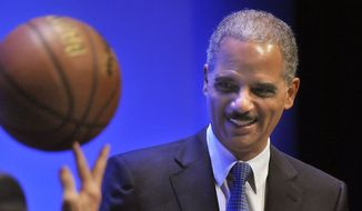 U.S. Attorney General Eric Holder is presented with a basketball as a token of appreciation by the University of Maine during a lecture in Orono, Maine, on Oct. 23, 2009. (Associated Press) **FILE**