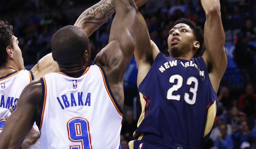 New Orleans Pelicans forward Anthony Davis (23) shoots as Oklahoma City Thunder center Steven Adams (12) and forward Serge Ibaka (9) defend during the fourth quarter of an NBA basketball game in Oklahoma City, Friday, Feb. 6, 2015.  New Orleans won 116-113. (AP Photo/Alonzo Adams)