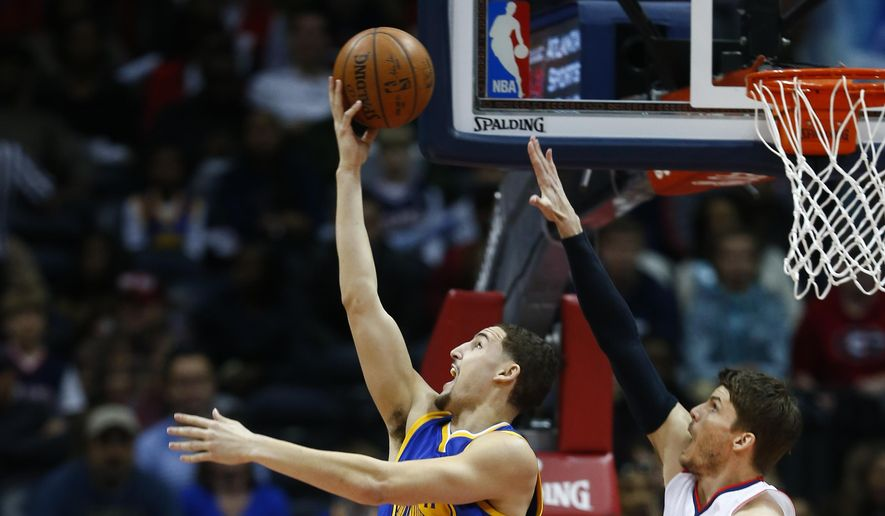 Golden State Warriors guard Klay Thompson (11) goes up for a shot as Atlanta Hawks guard Kyle Korver (26) defends in the first half of an NBA basketball game  Friday, Feb. 6, 2015, in Atlanta.  (AP Photo/John Bazemore)