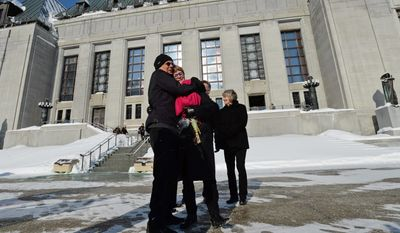 Lee Carter, right, and her husband Hollis Johnson embrace outside the Supreme Court of Canada, Feb. 6 in Ottawa. The high court unanimously strucktdown a ban on doctor-assisted suicide for mentally competent patients with terminal illnesses. Ms. Carter and her husband had accompanied her 89-year-old mother Kathleen (Kay) Carter, who suffered from spinal stenosis, to Switzerland in 2010 where assisted suicide is legal, to end her life. (AP Photo/The Canadian Press, Sean Kilpatrick)