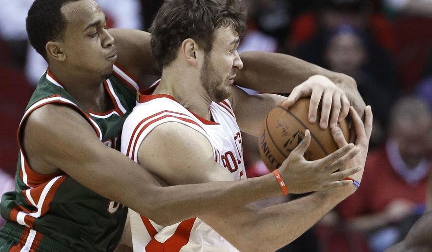 Milwaukee Bucks' John Henson, left, and Houston Rockets' Donatas Motiejunas battle for control of the ball during the first half of an NBA basketball game Friday, Feb. 6, 2015, in Houston. (AP Photo/Pat Sullivan)