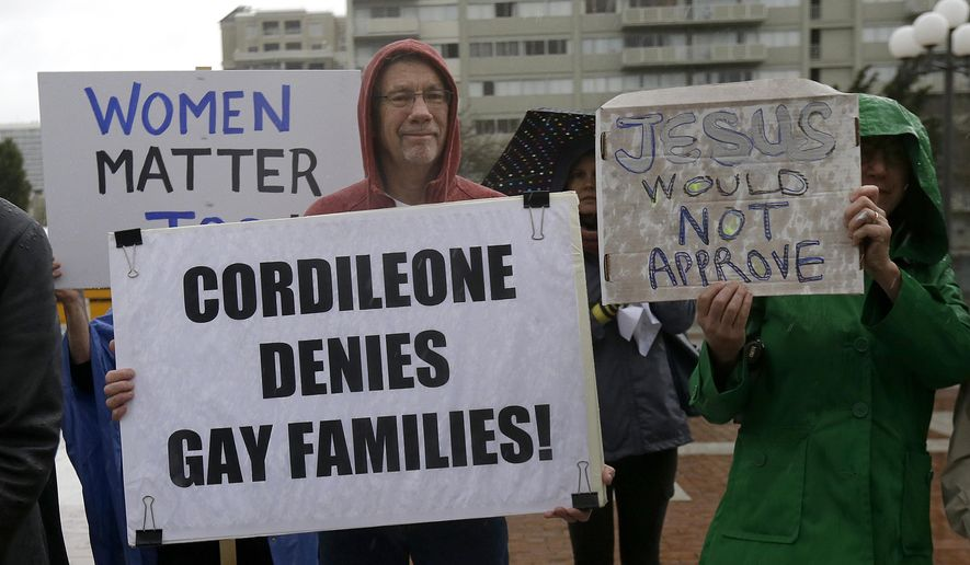 Billy Bradford, left, and others hold up signs as they gather with students and supporters at a vigil outside of St. Mary's Cathedral in San Francisco, Friday, Feb. 6, 2015. The Roman Catholic archbishop of San Francisco is getting pushback from some parents, students and teachers at parochial schools after unveiling faculty handbook language calling on teachers to lead their public and professional lives consistently with church teachings on homosexuality, same-sex marriage, abortion, birth control and other behaviors he describes as evil.  (AP Photo/Jeff Chiu)