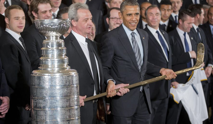 LA Kings head coach Darryl Sutter hands President Barack Obama, center, a hockey stick during a ceremony to honor both the 2014 NHL Champion Los Angeles Kings and 2014 MLS Cup Champion LA Galaxy in the East Room of the White House, on Monday, Feb. 2, 2015, in Washington.