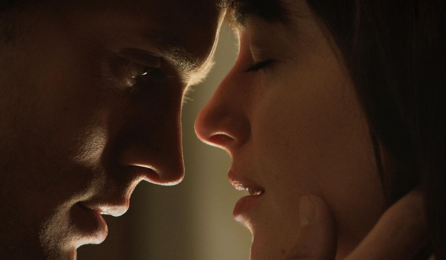 "In this image released by Universal Pictures and Focus Features, Jamie Dornan, left, and Dakota Johnson appear in a scene from ""Fifty Shades of Grey."" The ticket-buying site Fandango said pre-sales have propelled the movie into the 15-year-old company's Top 5 for R-rated selections. Several hundred screenings have already sold out from Tupelo, Mississippi, to Chattanooga, Tennessee, the company said. (AP Photo/Universal Pictures and Focus Features)"