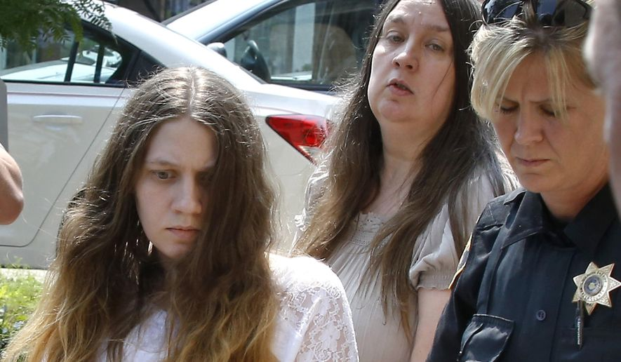 FILE-- In this Aug. 7, 2014 file photo, Mary C. Rader, left, and her mother, Deana Beighly, center, are escorted by sheriff's deputies from the courthouse to an awaiting police vehicle in Mercer, Pa. Rader is the mother of an 8-year-old boy who police say nearly starved. On Friday, Feb. 6, 2014, the mother and grandparents of a 7-year-old boy who was so malnourished that one doctor said he looked like a Holocaust survivor pleaded guilty to aggravated assault for failing to seek timely medical attention for him.  (AP Photo/Keith Srakocic,FILE)