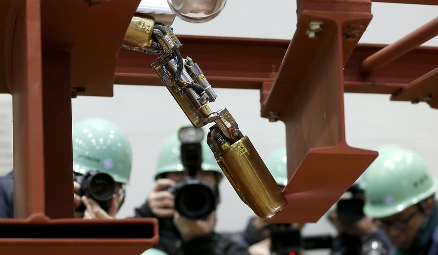 In this Thursday, Feb. 5, 2015 photo, photographers take photos of a remote-controlled robot that looks like an enlarged fiberscope crawling down into the mock-up of a primary containment chamber during a demonstration for the media at a government facility in Hitachi, Ibaraki Prefecture, northeast of Tokyo. The snake-like robot, developed by Japanese electronics giant Hitachi and its nuclear affiliate Hitachi-GE Nuclear Energy, is ready to examine in April the damage inside Unit 1 reactor at the Fukushima dai-ichi nuclear plant, wrecked by the march 2011 earthquake and tsunami. (AP Photo/Shizuo Kambayashi)