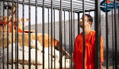 This still image made from video released by Islamic State group militants and posted on the website of the SITE Intelligence Group in this Tuesday, Feb. 3, 2015, file photo, shows Jordanian pilot Lt. Muath al-Kaseasbeh standing in a cage just before being burned to death by his captors. (AP Photo/SITE Intelligence Group, File)