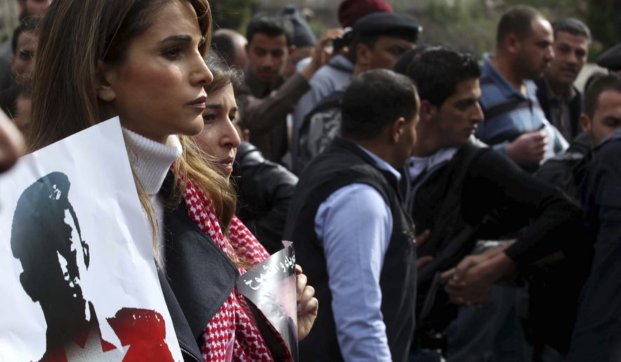Jordan's Queen Rania holds a picture of slain Jordanian pilot, Lt. Muath al-Kaseasbeh, during a march after Friday prayers in  Amman, Jordan, Friday, Feb. 6, 2015. Several thousand people - including the queen - marched in support of King Abdullah II after Muslim noon prayers. The crowd unfurled a large Jordanian flag and held up banners in support of the king's pledge of a tough military response to the killing of the pilot. (AP Photo/Raad Adayleh)