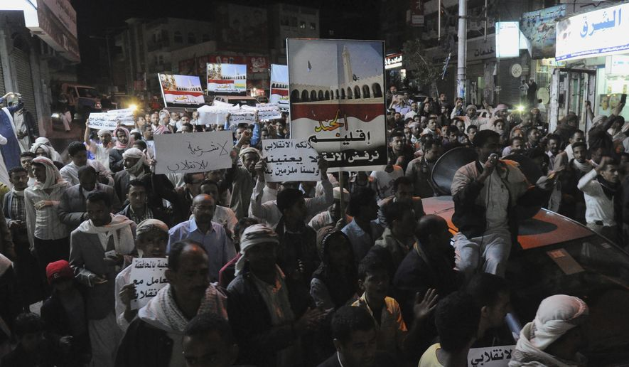 "Yemeni people hold a rally to protest against Shiite rebels' announcement of taking over the country in Taiz, Yemen, Friday, Feb. 6, 2015. Yemen's powerful Shiite rebels announced on Friday that they have taken over the country and dissolved parliament, a dramatic move that finalizes their monthslong power grab. Arabic writing on banners that reads, ""We reject the coup."" (AP Photo/Anees Mahyoub)"
