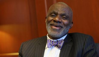 In this Jan 15, 2015, photo, Minnesota Supreme Court Justice Alan Page laughs during an interview in his chambers in St. Paul, Minn. Page, known as an NFL Hall of Famer with the Minnesota Vikings' Purple People Eaters defensive line from the late 1960s into the late 70s, has spent 22 years as the first black justice on the state's highest court. That chapter will come to an end in August when he hits the mandatory retirement age of 70. (AP Photo/Jim Mone)