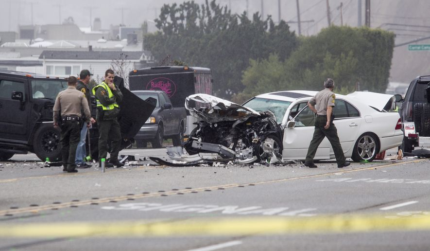 Los Angeles County Sheriff's deputies investigate the scene of a collision involving three vehicles in Malibu, Calif. on Saturday, Feb. 7, 2015. Officials said former Olympian Bruce Jenner was a passenger in one of the cars involved in the Pacific Coast Highway crash that killed one person. Mr. Jenner's publicist, Alan Nierob, says Jenner was unhurt. (AP Photo/Ringo H.W. Chiu)