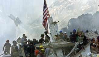 An American flag flies over the rubble of the collapsed World Trade Center buildings in New York in this Sept. 13, 2001, file photo. (AP Photo/Beth A. Keiser, File) ** FILE **