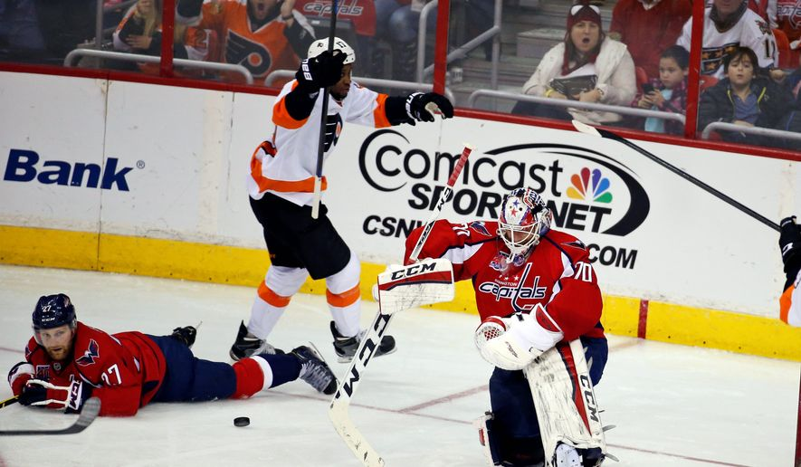 Capitals goalie Braden Holtby reacts after allowing a goal to Philadelphia right wing Wayne Simmonds as defenseman Karl Alzner lies on the ice, in the third period of the Flyers' 3-1 victory on Sunday. The Capitals managed a paltry 14-shots on goal as they saw their three-game winning streak snapped. (Associated Press Photographs)