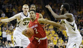 Maryland guard Melo Trimble drives to the basket past Iowa center Gabriel Olaseni (right) on Sunday. (Associated Press)