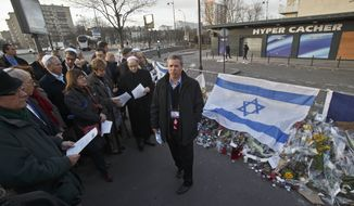 David Brown chair of Israel and Overseas operation of the Jewish Federations of North America, right, speaks to members of the Federation as they visit the site of the kosher grocery store in Paris, Sunday Feb. 8, 2015, where four people where killed in a terror attack. Member of the Jewish Federation of North America traveled to Paris to show support with victims of the terror attack a month ago. (AP Photo/Michel Euler)