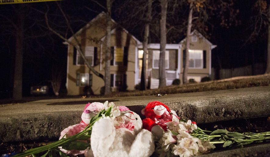 Flowers and teddy bears lay on the street outside the home of a shooting scene where authorities say five people are dead, including the gunman, in Douglasville, Ga. on Saturday, Feb. 7, 2015. Douglas County Sheriff's Lt. Glenn Daniel said the gunman shot six people before fatally shooting himself, and the two surviving victims are children, but children are also among the dead. (AP Photo/David Goldman)