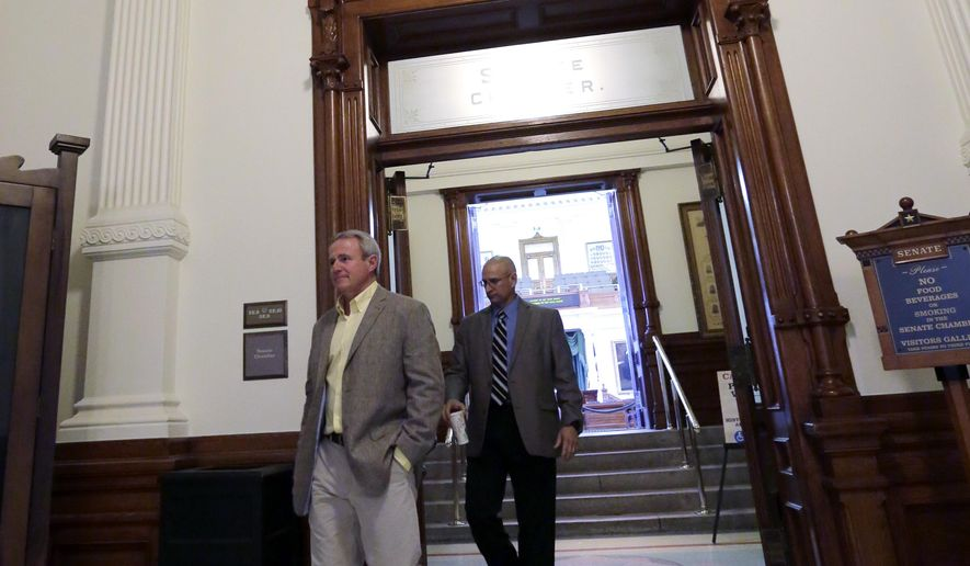 Michael Morton, left, who was exonerated of murder by DNA evidence after spending 25 years in prison, leaves the Texas Senate following a news conference with Sen. Rodney Ellis (D-Houston), Monday, Feb. 9, 2015, in Austin, Texas. Ellis has filed legislation intended to fix issues created by a 2011 law he authored that makes crime-scene DNA testing difficult for convicts. (AP Photo/Eric Gay)