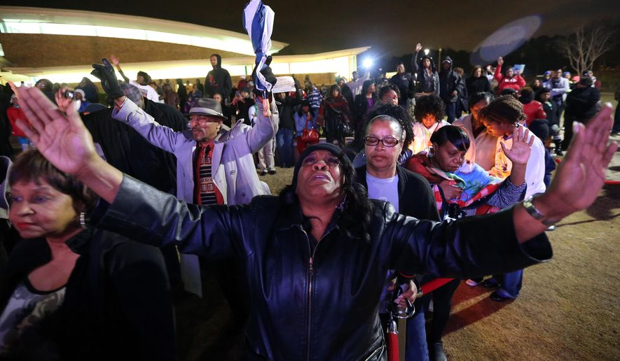 Denice Matthews of Riverdale, Ga., joins several hundred people at the Riverdale amphitheater for a prayer vigil for Bobbi Kristina Brown on Monday, Feb. 9, 2015.(AP Photo/Atlanta Journal-Constitution, Ben Gray)