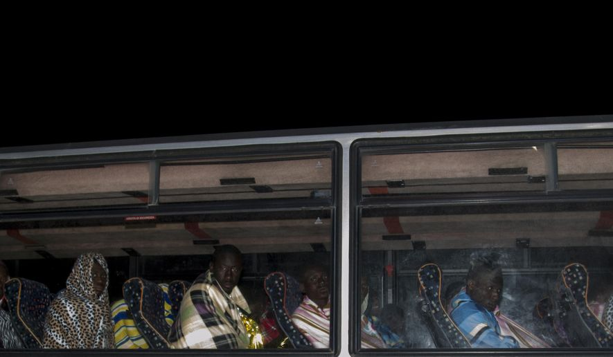 Some of the migrants that were rescued at sea sit on a bus in the harbor of Lampedusa Monday, Feb. 9, 2015. At least 29 migrants have died from hypothermia while traveling from North Africa to Italy aboard a smuggler's life raft in heavy seas, amid a surge of migrants making the dangerous sea crossing despite the harsh winter conditions. The victims were among 106 people packed aboard an inflatable life raft who were trying to cross the Mediterranean in rough seas and freezing temperatures, Italian coast guard Cmdr. Filippo Marini said Monday. The migrants had summoned help late Sunday via satellite telephone while still off Libya's coast. (AP Photo/Mauro Buccarello)